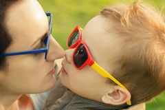 The son kisses and hugs his mom in sunglasses outdoors. Mother and her child having fun together. Little kid express the love to his mommy royalty free stock photography