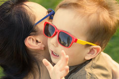 The son kisses and hugs his mom in sunglasses outdoors. Mother and her child having fun together. Little kid express the love to his mommy Stock Photos