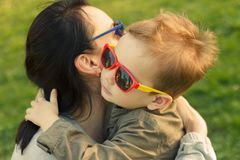 The son kisses and hugs his mom in sunglasses outdoors. Mother and her child having fun together. Little kid express the love to his mommy stock image