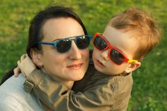 The son kisses and hugs his mom in sunglasses outdoors. Mother and her child having fun together. Little kid express the love to his mommy Royalty Free Stock Photo
