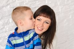 Son kisses mother. Mother smiling, close-up shot Royalty Free Stock Photo