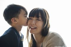 Son kissing cheek his mom with love Stock Image