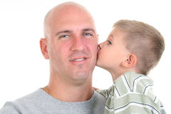 Son Kissing Dad On The Cheek. Four year old boy kissing his dad on the cheek.  Close-up, headshot over white Royalty Free Stock Image