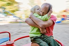 Son kissing father. Little boy embracing and kissing his father while riding on carousel Royalty Free Stock Photography