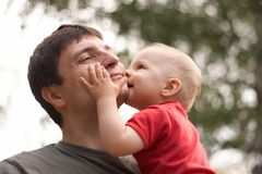 Son kissing his father. Smiling son kissing his father Royalty Free Stock Photos