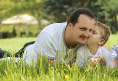 Son kissing his father outdoor. Son kissing his father among green grass Royalty Free Stock Image