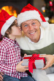 Son kissing his father after receiving a christmas gift. At home in the living room Royalty Free Stock Photography