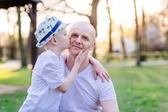 Son kissing his father. Father`s Day. Happy family in the park stock photo