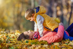 Son is kissing his mother. In autumn park Royalty Free Stock Photography