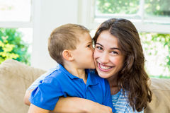 Son kissing his mother in living room. Affectionate son kissing his mother in living room Stock Photography