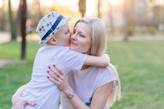 Son kissing his mother. Mother`s Day. Happy family in the park royalty free stock image