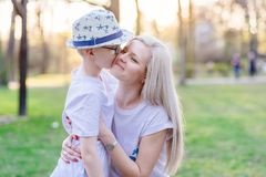 Son kissing his mother. Mother`s Day. Happy family in the park stock photography