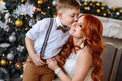 Son kissing his mother near Christmas tree. In a white room with Christmas decorations Royalty Free Stock Photo