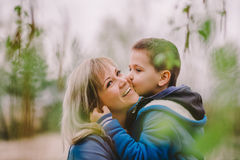 Son is kissing his mother outdoor Stock Photo