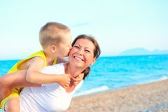 Son kissing and hugging her mother Royalty Free Stock Photos