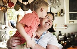 Son kissing mommy in the kitchen royalty free stock image