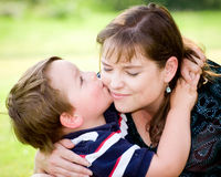 Son kissing mother. While playing outside on Mother's Day Royalty Free Stock Image