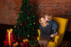 Son kissing mother near Christmas tree. Son kisses his mother is sitting near the Christmas tree Stock Image