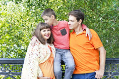Son kissing pregnant mother. Happy family son kissing pregnant mother in summer embankment Royalty Free Stock Images