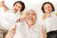 Son kissing their father. The father and son laying on the bed showing thumb up Royalty Free Stock Photo