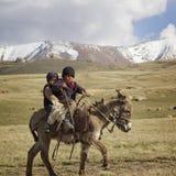 SON KUL LAKE, KYRGYZSTAN -  JUNE 10. Two children riding a donke. Y, June 10 2014, Son Kul lake, Kyrgyzstan Royalty Free Stock Image