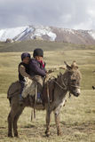 SON KUL LAKE, KYRGYZSTAN -  JUNE 10. Two children riding a donke Royalty Free Stock Photography