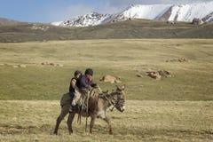 SON KUL LAKE, KYRGYZSTAN -  JUNE 10. Two children riding a donke Royalty Free Stock Image