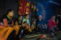 Son La,越南- 2016年1月13日:H `坐在他们的房子里面的火附近的mong家庭在H ` mong在Ta许的新年假日期间 库存照片