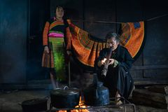 Son La, Vietnam - Jan 13, 2016: H`mong man smokes next to the fire and his granddaughter inside his house in Bac Yen district.  Stock Photo