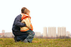 Son on lap of father outdoor. In city Stock Photography