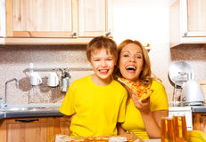 Son and laughing mother holding slice of pizza Royalty Free Stock Photo