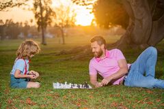 Son laying on grass and playing chess with father. Little boy play chess with parent. Cognitive development