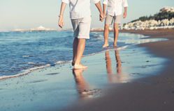 Son legs go to his father on the sea surf line close up image Stock Photos