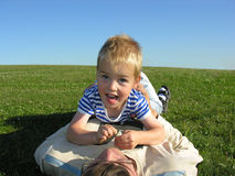 Son lie on father. On green grass stock images