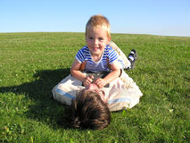 Son lie on father on green grass 2. Smile son lie on father on green grass 2 Royalty Free Stock Image