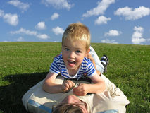 Son lie on father on green grass. Son lies on father on green grass with clouds Royalty Free Stock Photo