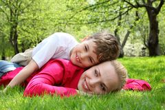 Son lies on back of mother lying in park. Son lies on back of mother lying on grass in park in spring Royalty Free Stock Images