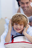 Son listening to music in bed with his father. Son listening to music in bed with headphones on with his father Royalty Free Stock Images