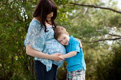 Son Listening to Pregnant Mother's Belly. Young son listening to belly of pregnant outdoors in park royalty free stock photos