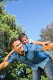 Son lying on his fathers back Royalty Free Stock Image