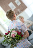 Son making flower surprise to his mother. Son hiding bouquet to surprise mommy on mother's day Royalty Free Stock Image