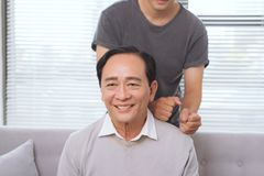 Son massaging father shoulder, sitting on sofa. Son massaging father shoulder, sitting on sofa Royalty Free Stock Photo
