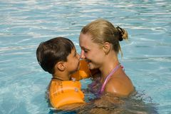 Son and mom play in the pool. Son and mom swim and play in the pool Royalty Free Stock Photography