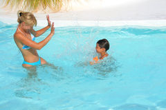 Son and mom swim and play in  pool Stock Image