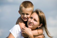 Son with mother. The little boy embraces beautiful mother from  back Stock Photography