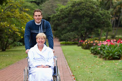 Son and mother. Son pushing senior mother on wheelchair outdoors for a walk stock photo