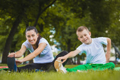 Son and mother are doing exercises in the park Stock Photo