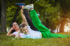 Son and mother are doing exercises in the park royalty free stock photos