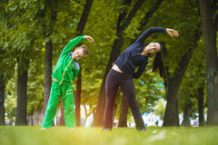 Son and mother are doing exercises in the park. Son and mother are doing exercises in the summer park Royalty Free Stock Photography