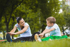 Son and mother are doing exercises in the park. Son and mother are doing exercises in the summer park Stock Image